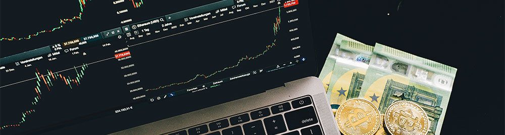 Cash with crypto market shown on screen